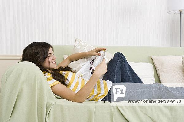 Teenagermädchen entspannt auf dem Sofa Lesemagazin