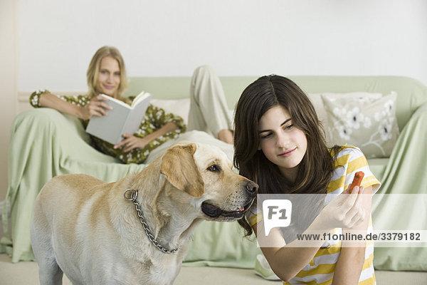 Teenagermädchen bietet Hundekuchen für Haustiere an