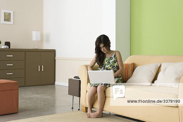 Teenager Mädchen mit Laptop im Wohnzimmer