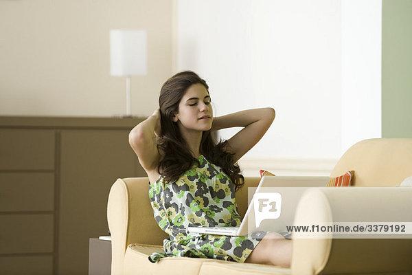 Teenager Mädchen entspannen auf dem Sofa mit Laptop