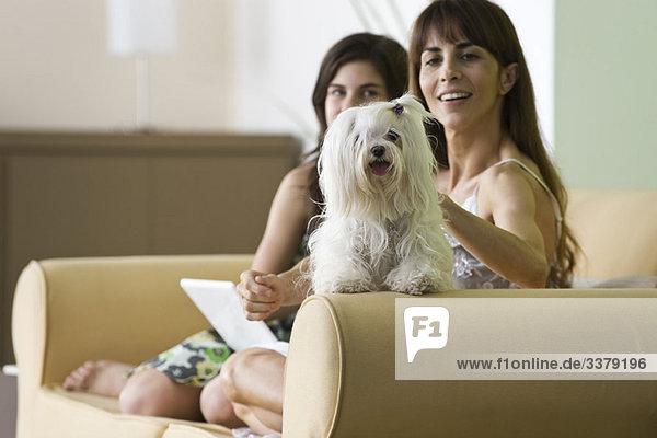 Frau entspannt sich mit Haushund und Teenager-Tochter