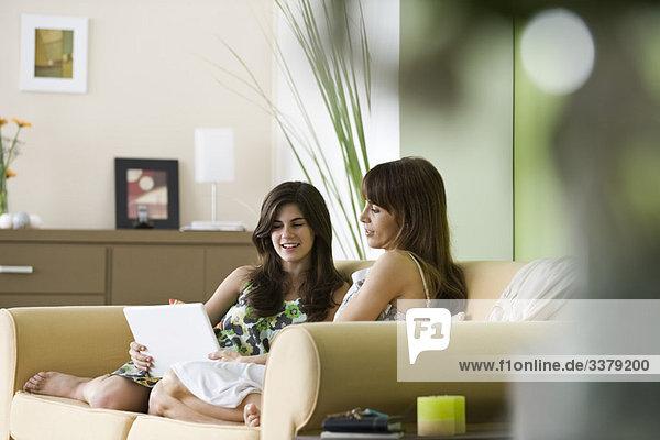 Mutter und Tochter zusammen auf dem Sofa mit Laptop-Computer