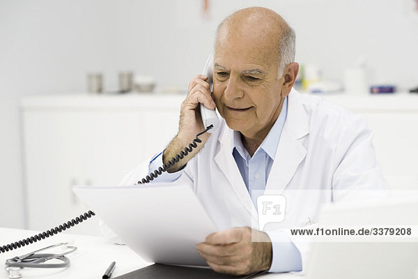 Arzt im Büro nimmt Telefonanruf entgegen