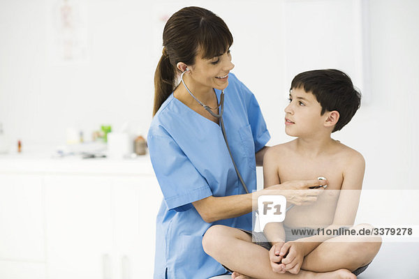 Krankenschwester untersuchender Junge mit Stethoskop
