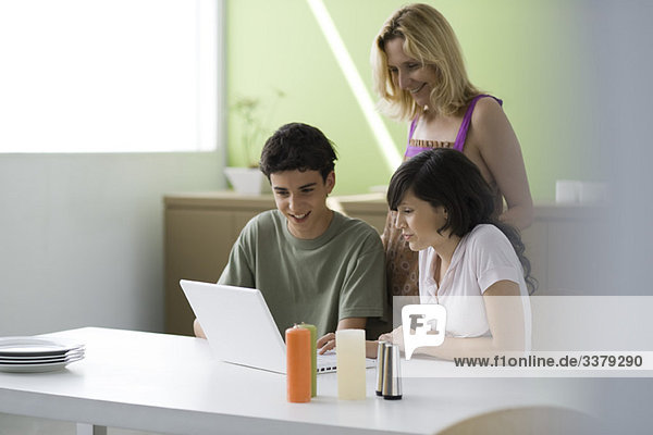 Mutter beobachtet Sohn und Tochter im Teenageralter mit Hilfe eines Laptops