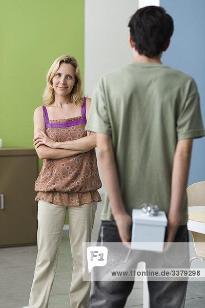 Teenager-Sohn bereitet sich darauf vor  Mutter ein Geschenk zu machen.