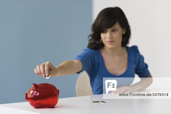 Teenagermädchen legt Münze ins Sparschwein