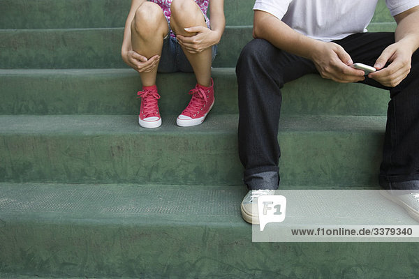 Teenager-Paar auf einer Treppe sitzend Teenager-Paar auf einer Treppe sitzend