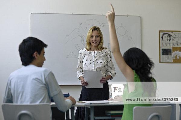 Gymnasiallehrer im Klassenzimmer  ein Schüler hebt die Hand