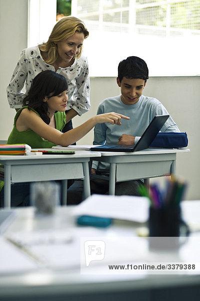 Lehrer und Schüler mit Laptop im Unterricht