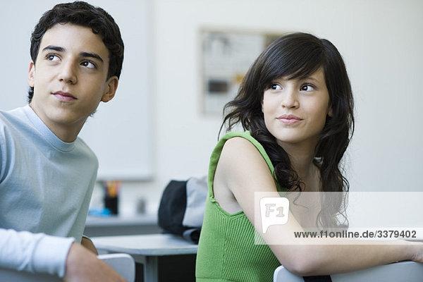 Gymnasiasten in der Klasse  die interessiert über die Schultern schauen