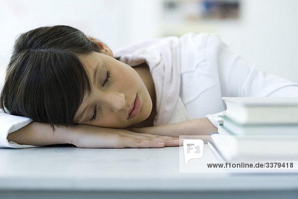 Gymnasiastenschlaf mit Kopf auf dem Schreibtisch  Bücherstapel im Vordergrund