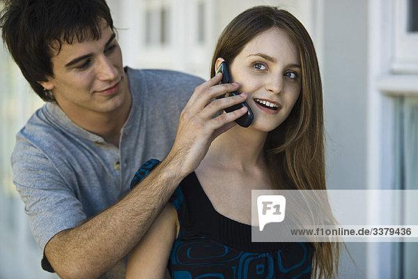 Junger Mann hält Handy an das Ohr der Freundin