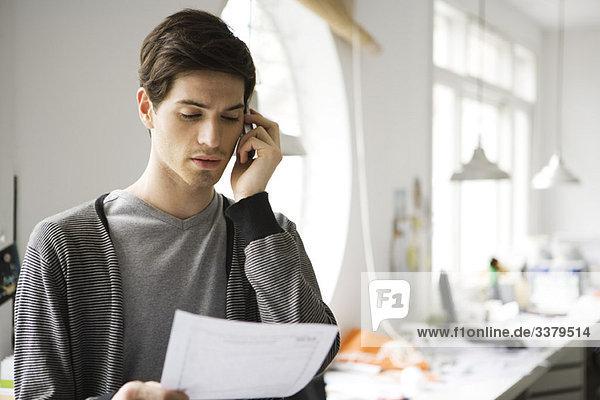 Ein Mann mit einem Dokument  der auf dem Handy spricht.