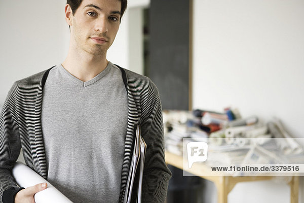 Man carrying rolled up blueprint under arm