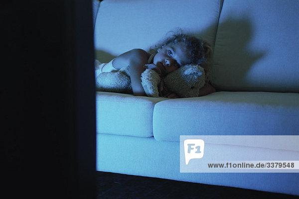 Mädchen auf dem Sofa liegend mit Teddybär  fernsehend