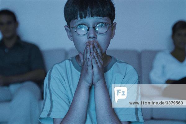 Junge schaut mit den Händen über dem Mund fern