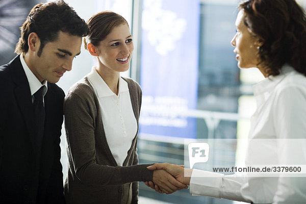 Geschäftsfrau begrüßt junges Paar