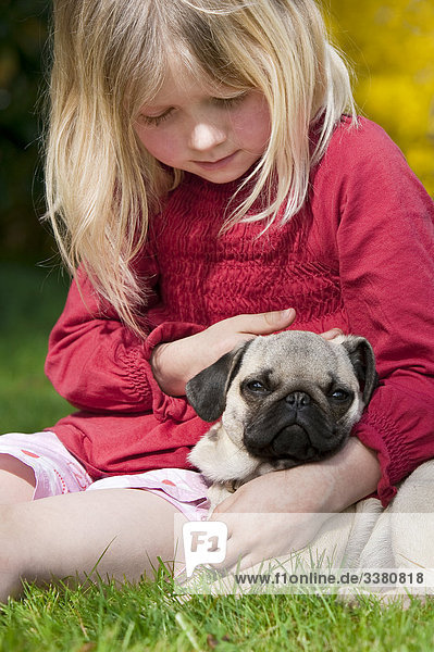 Girl and pug on a meadow