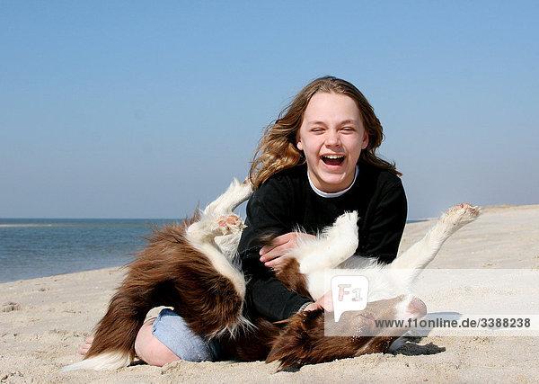 Mädchen und Border Collie spielen am Strand