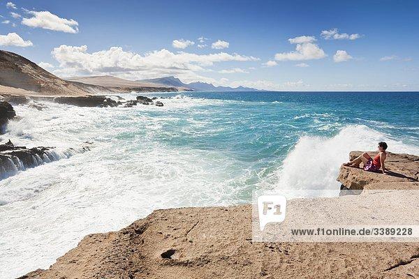 Frau sitzt auf einem Felsen an der Westküste von Fuerteventura  Spanien  Erhöhte Ansicht