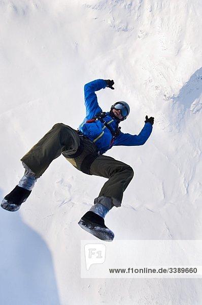 Mann gegen eine Verhüllung von Schnee  Schweden nach hinten fallen.