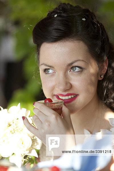 Junge Fraue hält ein Glas mit einem Dessert  Porträt