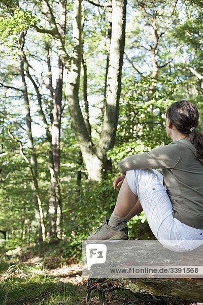 Frau im Wald sitzend