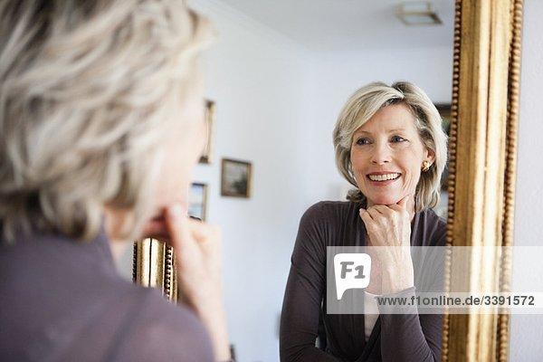 Senior Lady schaut in den Spiegel Senior Lady schaut in den Spiegel