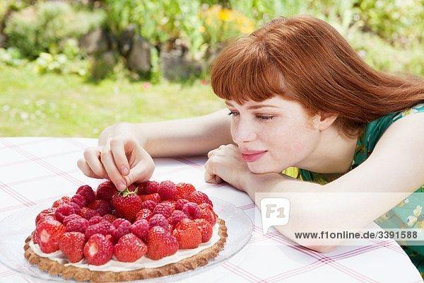 junge Frau  die Erdbeeren pflückt.