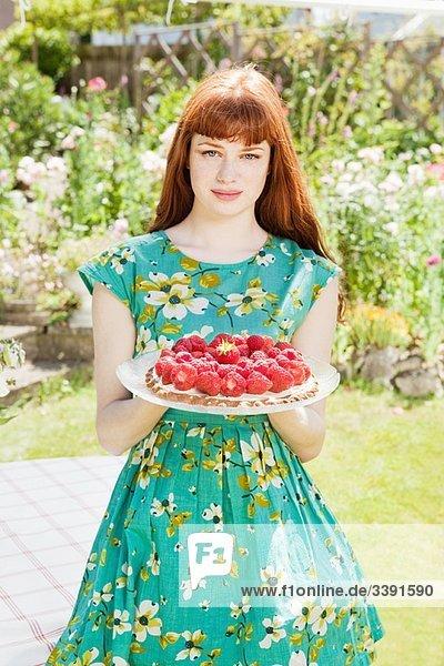 Frau steht Erdbeertorte im Garten.