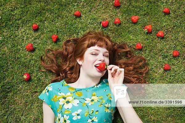 Mädchen im Gras umgeben von Erdbeeren