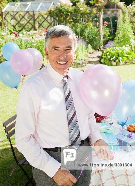 reifer Mann mit Luftballons.