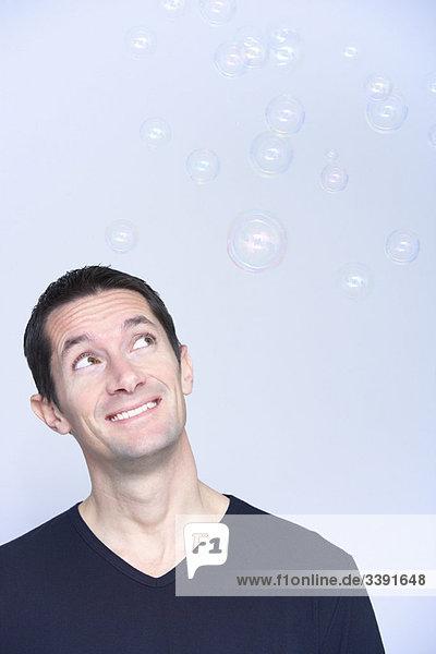 lächelnder Mann mit Blick auf Blasen