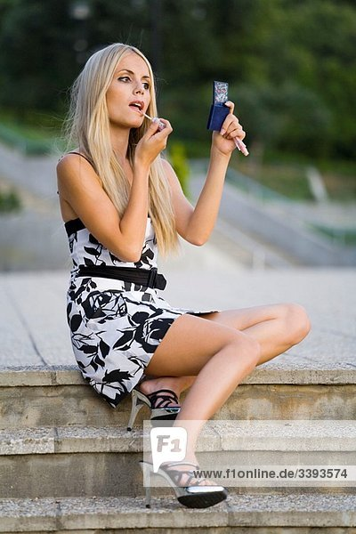 Applying makeup while sitting on staircase young woman