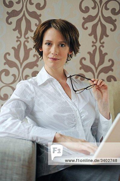 Brünette Frau mit Brille und Laptop