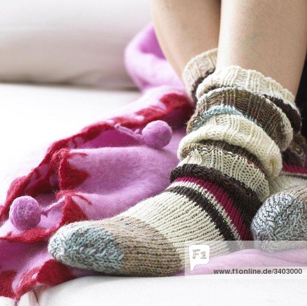 Füsse in geringelten Socken  mit rosa Plaid