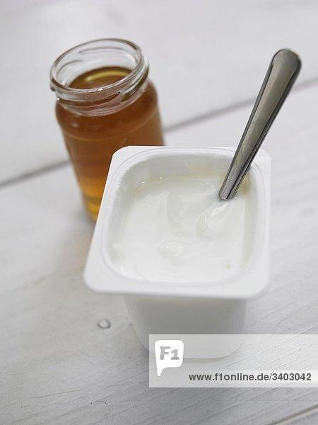 Becher mit Naturjoghurt und Löffel (im Hintergrund Honigglas)