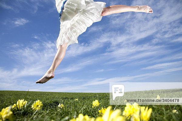 junge Frau im Park springen auf Rasen