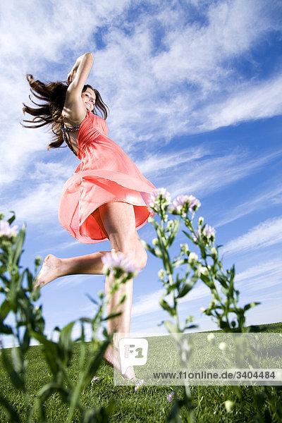 Portrait einer jungen Frau tanzen im park