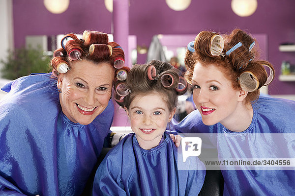 portrait of child and two woman with curlers in their hair