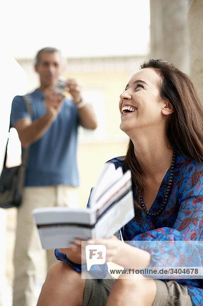 Portrait einer jungen Frau mit Reiseführer