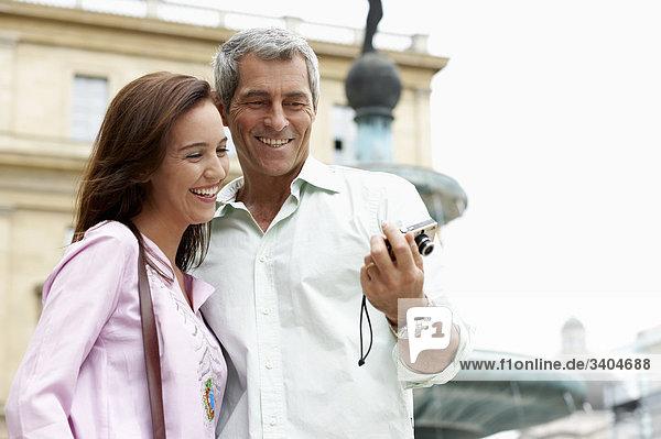Paar im Urlaub überprüfen Bild von sich selbst auf digital-Kamera
