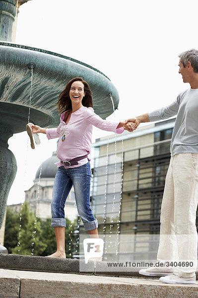 Paar in Frau Großstadt barfuss laufen auf Brunnen