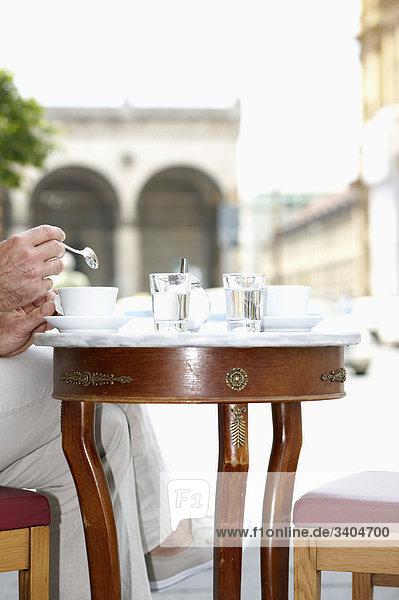Detail des Menschen an Cafe Tisch sitzend