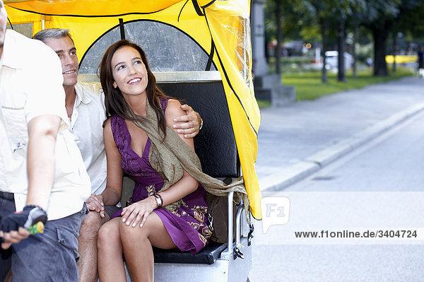 paar fahren durch Stadt in trishaw