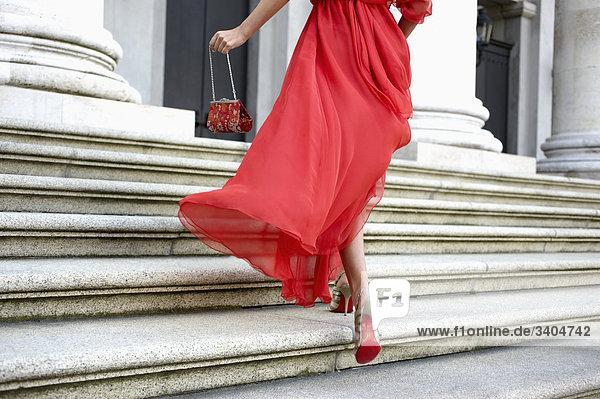 Detail der junge Frau im roten Kleid gelaufen Treppen des Theaters