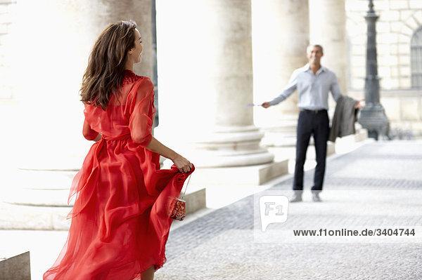 junge Frau im roten Kleid läuft auf Mann unter Arkaden des Theaters