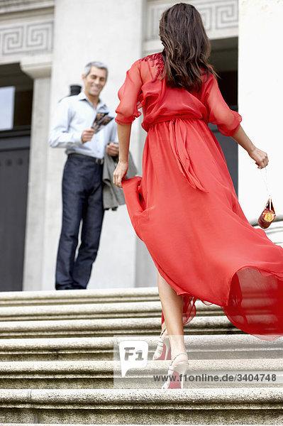 Rückansicht der junge Frau im roten Kleid gelaufen Treppen des Theaters in Richtung Mann