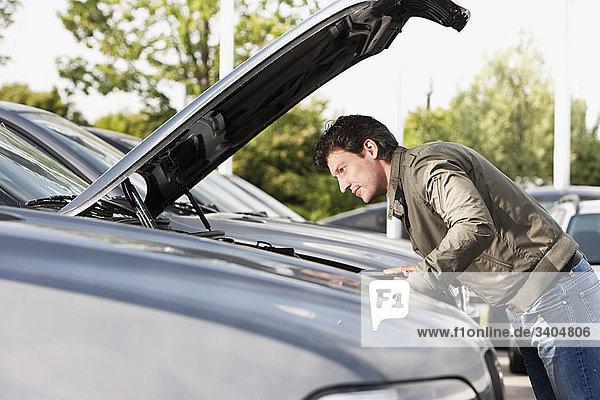 Mann bei Überprüfung Engine Auto Autohändler